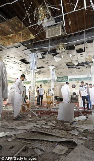 Saudi men gather around debris following a blast inside a mosque, in the mainly Shiite Saudi Gulf coastal town of Qatif, 400 kms east of Riyadh