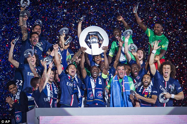 PSG defender Zoumana Camara (centre) holds the Ligue 1 trophy aloft following the win over Reims