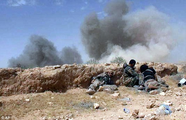 Battle:Islamic State fighters take cover during a battle against Syrian government forces on a road between Homs and Palmyra on Wednesday, shortly before they seized the city