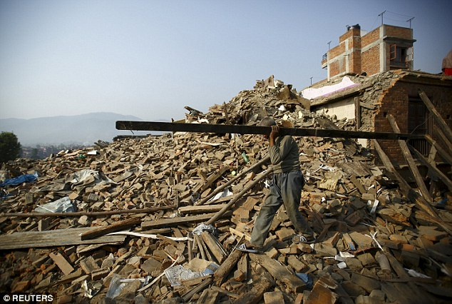 A man carries a block of wood recovered from his house as he walks through the debris in Nepal