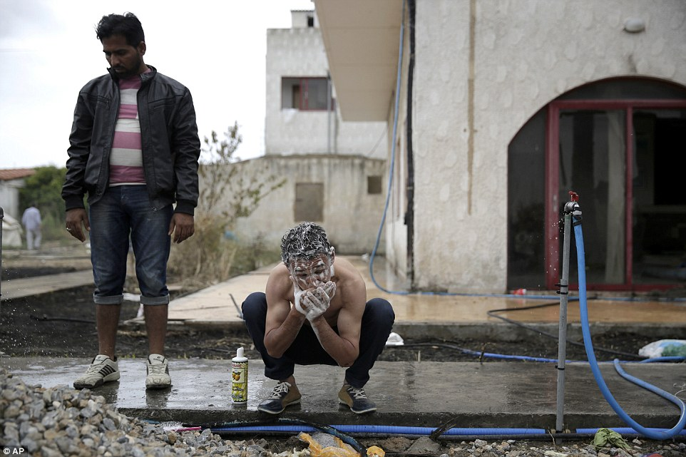 Squalid conditions: With no hot water, the migrants wash outside using a garden hosepipe
