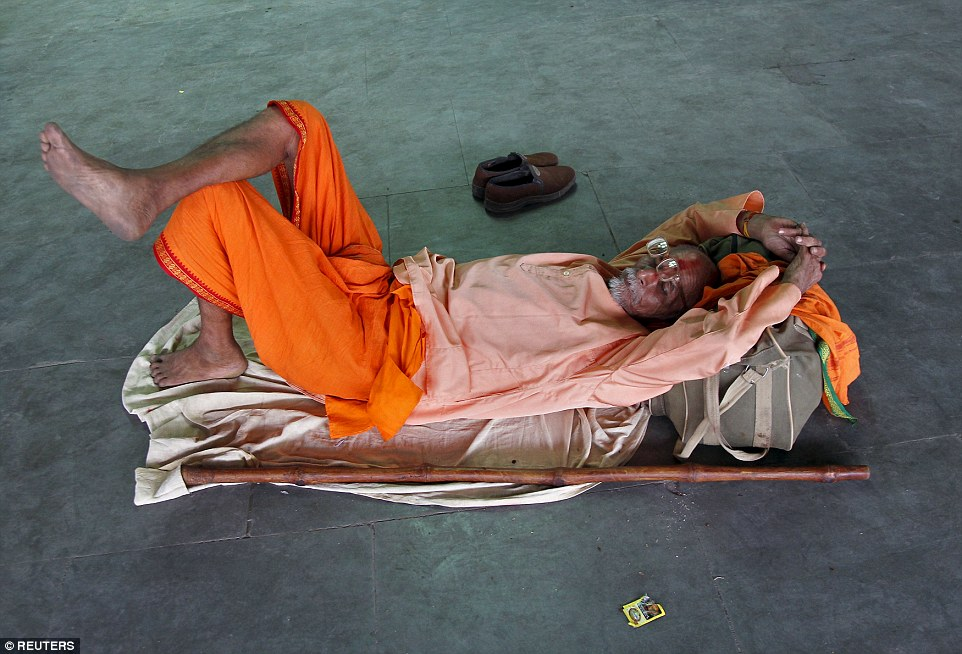 A Hindu holyman is pictured sheltering from the blistering sun in Allahabad, India. More than 1,100 people have now died in the heatwave