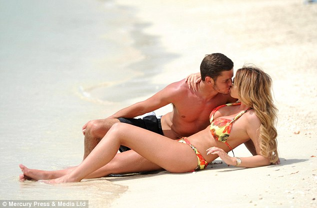 Scorching: The pair were caught smooching as they lay out on the golden sands