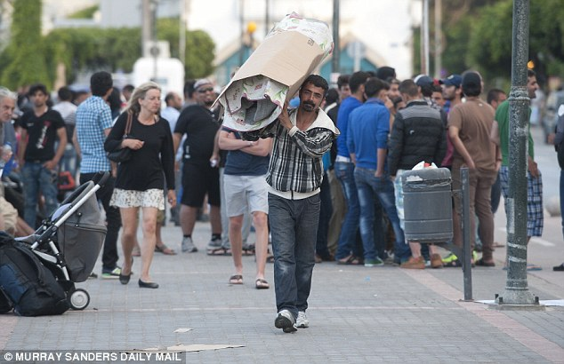 A man carries all of his possessions over his shoulder as he walks amongst tourists and migrants in Kos