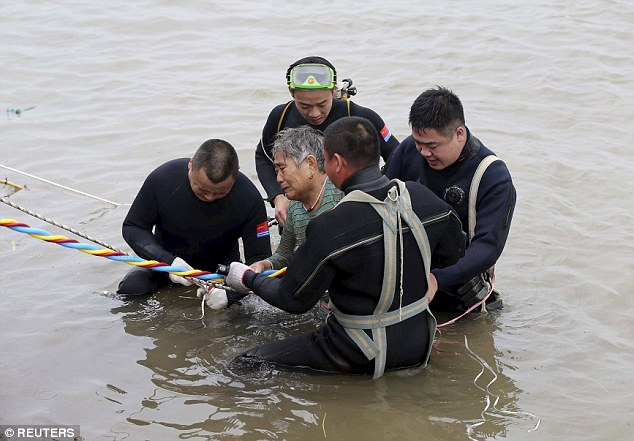 Survivor: An elderly man is pulled from the river, as divers comb the capsized ship for passengers