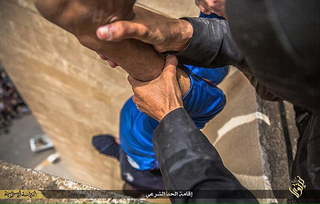 Disturbing: In a photo taken in the city of Mosul,  a gay man is dangled over the edge of a building by his ankles