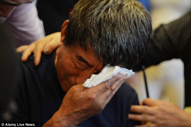 Distraught: Wu Jianqiang, 58, described how his wife pushed him out of the ferry so that he could be rescued