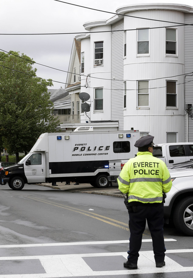 A police officer stands near a multi-storied home on Tuesday in Everett, Massachusetts, being searched by authorities in connection with a man shot and killed earlier in the day in Boston.David Wright was taken into custody at the home late on Tuesday