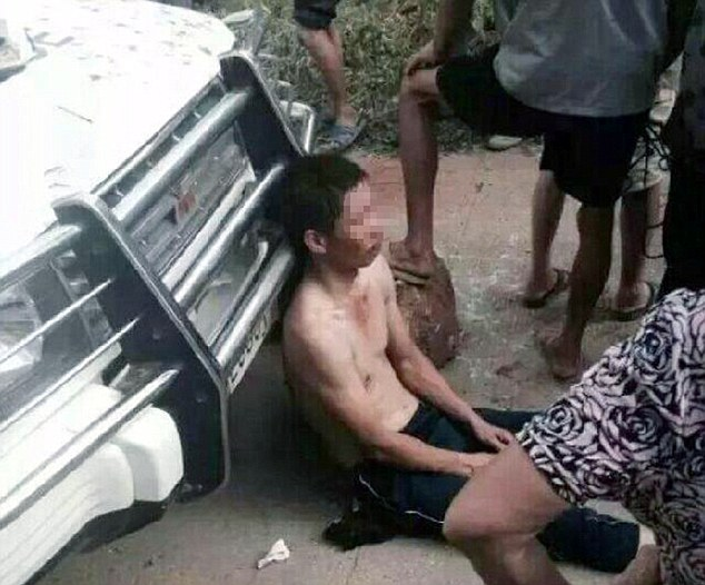 The other thief is seen slumped against a car surrounded by villagers. The pair were reportedly subjected to a brutal nine hour beating