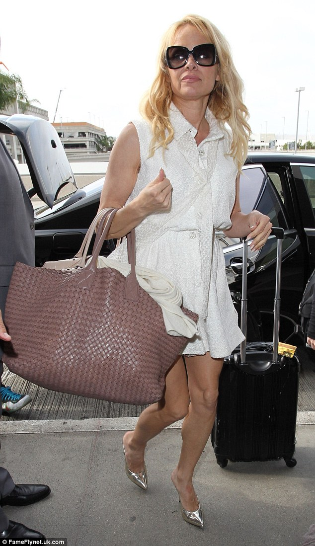 Pamela Anderson Shows Off Her Legs In A White Dress At LAX