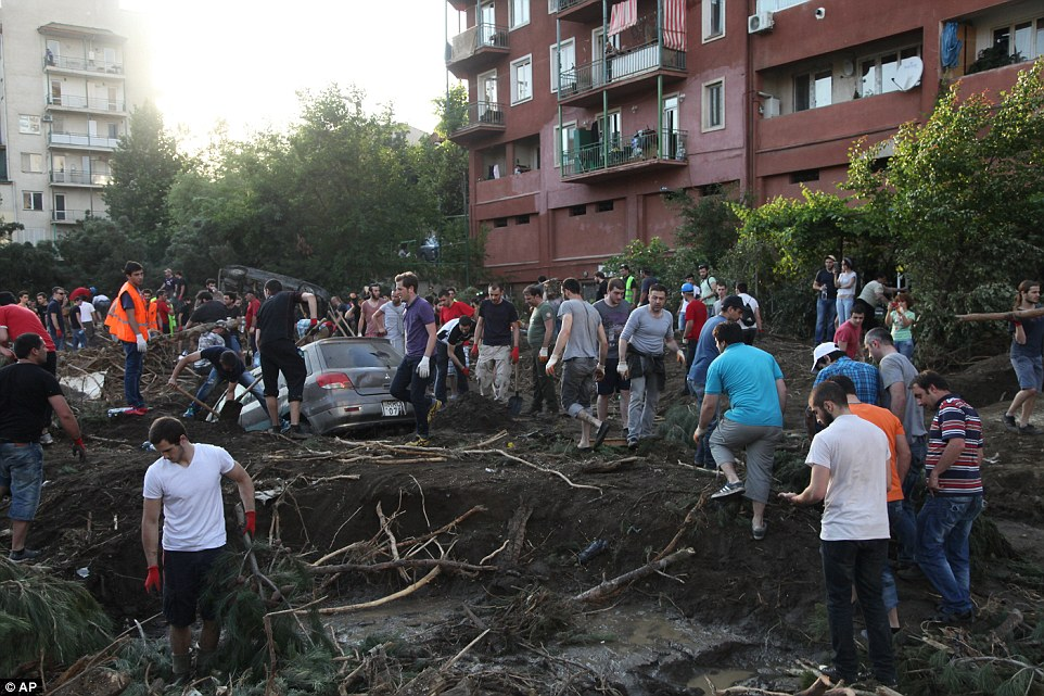 Hundreds of people worked together as they worked to clean a flooded area and dig out a car left submerged in the mud