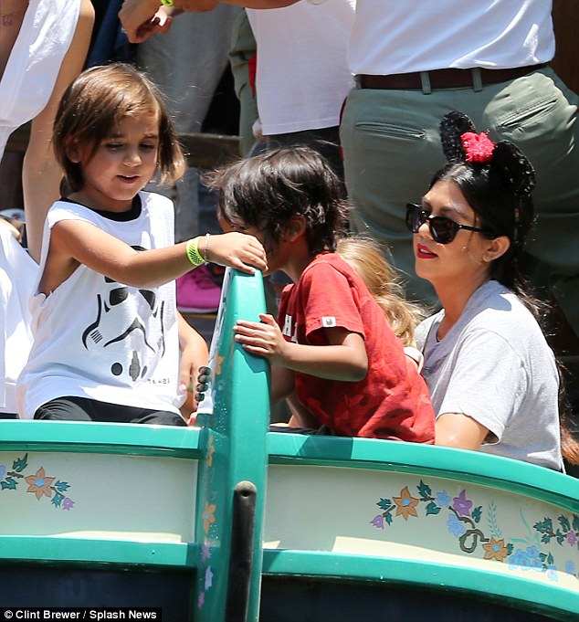 Having fun? Kourtney Kardashian (pictured right) was also spotted on the attraction as she was joined by five-year-old son Mason (left)