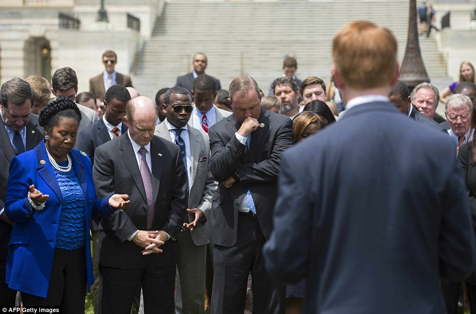 Moved: US Congressman Jeff Denham (center) prays with Senator Chris Coons (2nd left) and Congresswoman Shelia Jackson Lee (left) in front of the US Capitol in Washington, DC during a moment of silence for the victims on Thursday