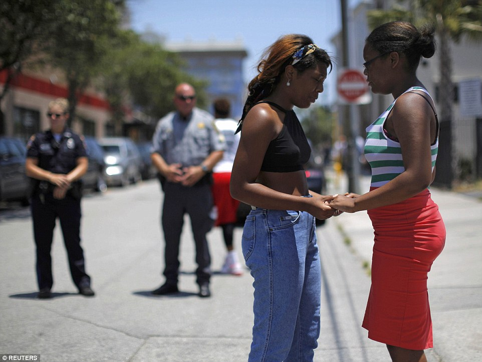 Together: Mourners hold hands as they pause outside Morris Brown AME Church during a vigil on Thursday