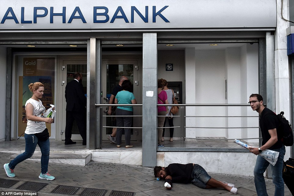 Desperate measures: People withdraw cash from ATM machines in central Athens  as a beggar lays on the pavement