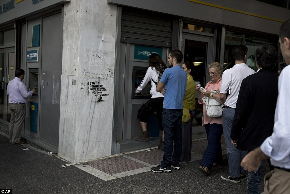 Run on the banks: People line up at an ATM outside a branch of the National Bank, in central Athens, after Greece failed to secure a deal with bailout creditors, prompting the European Union to call an emergency leaders' meeting for Monday