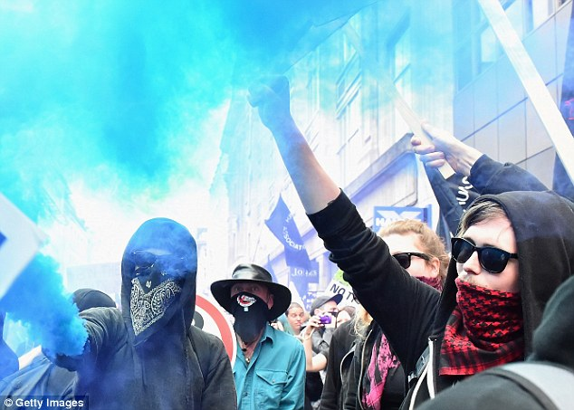 Protesters sprayed bright blue smoke into the crowd and covered their mouths with scarves