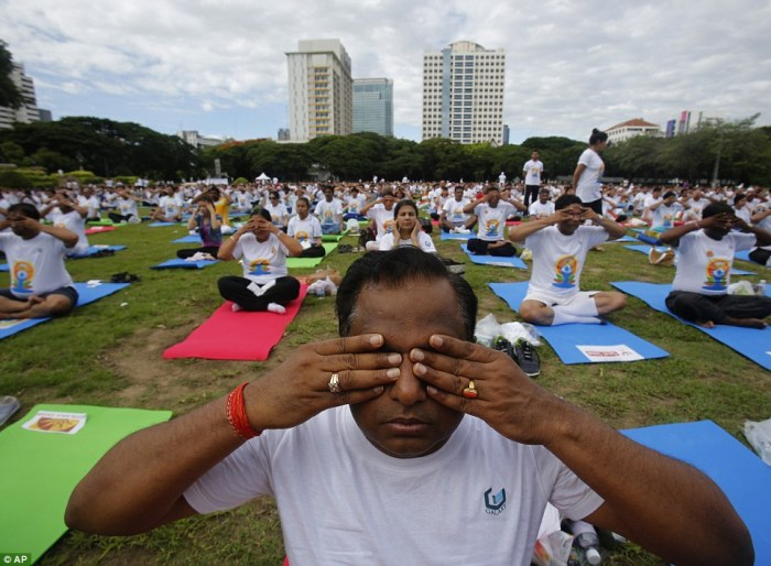 Thousands of people participate in a yoga exercise at Chulalongkorn University field, marking the International Day of Yoga in Bangkok