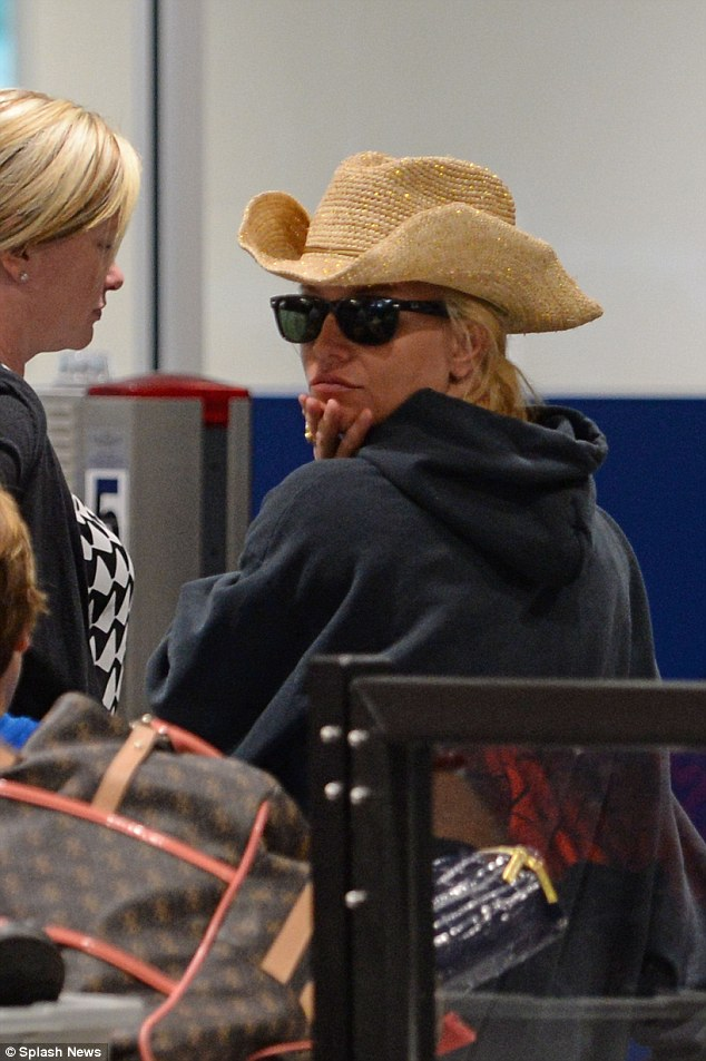 Even cowgirls get the blues: Britney Spears looks glum in a straw stetson as she steps out for the first time since shock split with Charlie Ebersol at New Orleans airport on Wednesday