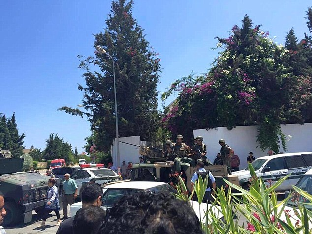 Tunisian troops stand guard outside the hotel in an armoured car after the terror attack