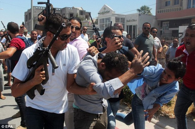 Tunisian security forces escort a man through the streets of Sousse as he is attacked by a woman