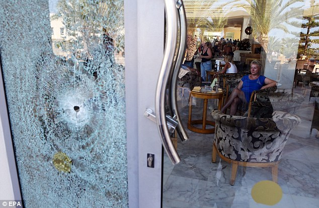Onslaught: One of the survivors of the massacre on a beach in Tunisia sits inside the Imperial Marhaba Hotel, where a window was smashed by gunfire