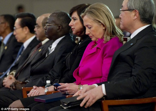 US Secretary of State Hillary Clinton checks her Blackberry phone alongside Korean Foreign Minister Kim Sung-hwan in November 2011 while on an official trip to South Korea