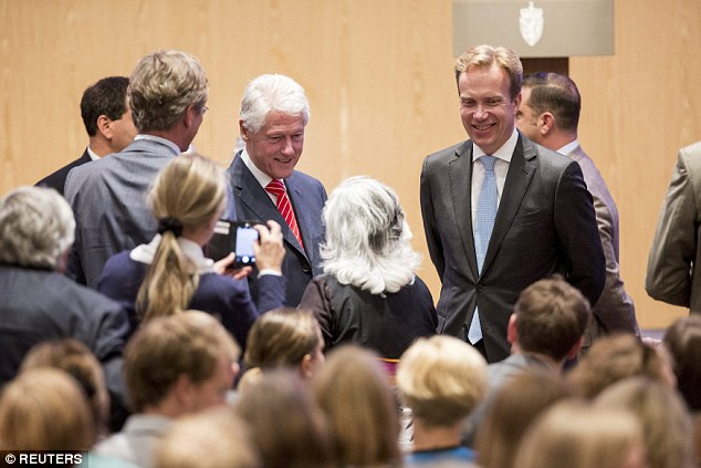 Arm's length: Bill Clinton in Oslo, Norway, today with Norwegian foreign minister Boerge Brende. The emails show he and Hillary often communicated to each other through their aides.