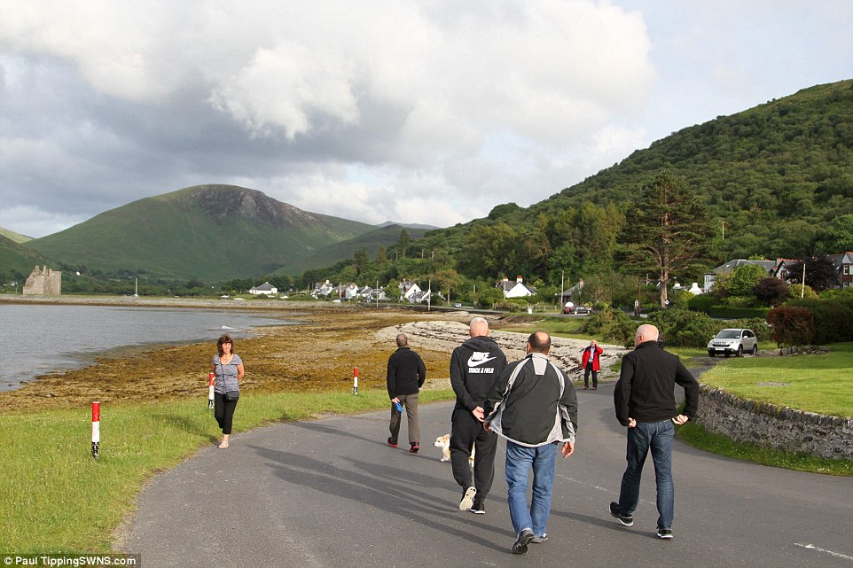 Unlikely visitor: A resident smiles at the group as they cross paths on a deserted road on Arran this morning where Mr Abramovich is holidaying