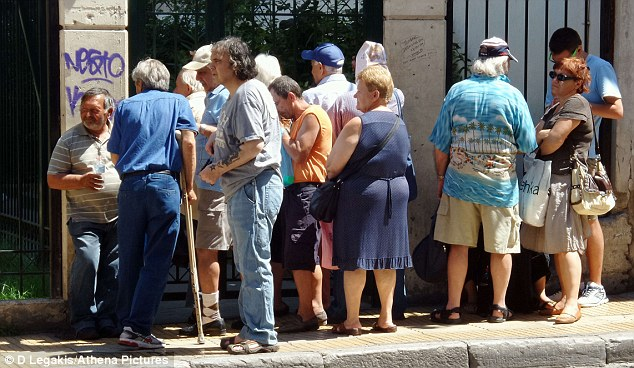 Needy: A crowd of people queue outside a soup kitchen in Athens. The charity feeds at least 1,500 people a day, helping suffering Greeks affected by austerity as well as the homeless, tramps and the mentally ill