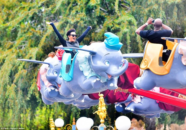 Mom came too: Kris flung her arms up when on the Dumbo ride inside Fantasyland; while her boyfriend Corey Gamble took a photo of her