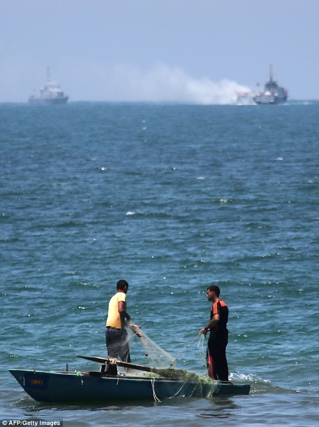 Pescadores palestinos a sus actividades como un buque de guerra egipcio acerca al buque patrulla afectada