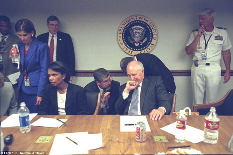 Advice: Cheney holds his hand to chin as his top lawyer, David Addington (seen kneeling), starts to secure the legal authority response