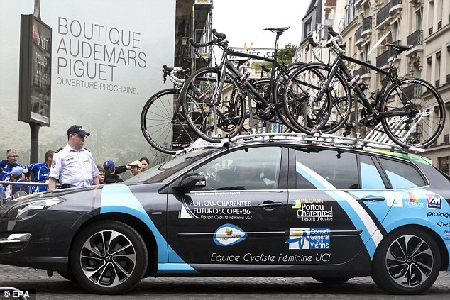 Race: A team car passes a police officer on guard after the incident. Tour de France director said he did not think the shooting would have any impact on the race, which will start at 2.35pm GMT from Sevres