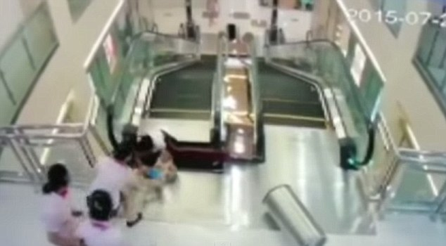 Desperate to help: Staff at the department store in Jingzhou struggled to help the woman, after she thrust her child to safety as her body dangled over the escalator machinery