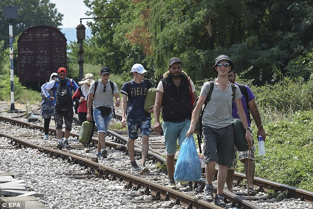 Los migrantes caminan sobre las vías del tren en la estación de tren en Gevgelija.  Grecia e Italia son los principales puntos de entrada para los solicitantes de asilo con destino a Europa y los migrantes económicos.  Después de que hayan llegado al bloque, muchos comienzan a hacer su camino a los países más ricos de Europa Occidental