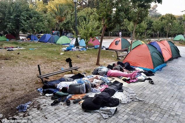 Los migrantes duermen en un parque de Atenas, donde encontraron un refugio temporal después de llegar de las islas griegas