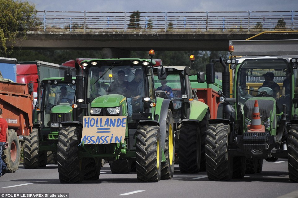 On the road: Tractor drivers blocked the main highways in the eastern Moselle region today, calling on President Francois Hollande to protect their livelihoods, as food prices soar across the country