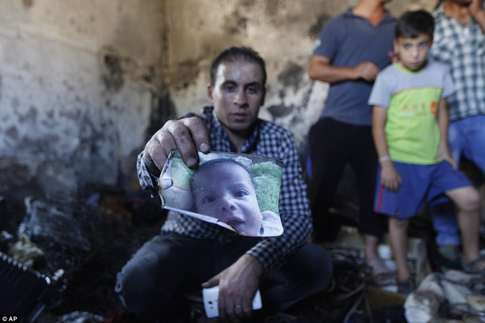 Burned alive: A relative holds up a photograph of 18-month-old Ali Dawabsheh who died in an arson attack by suspected Jewish extremists