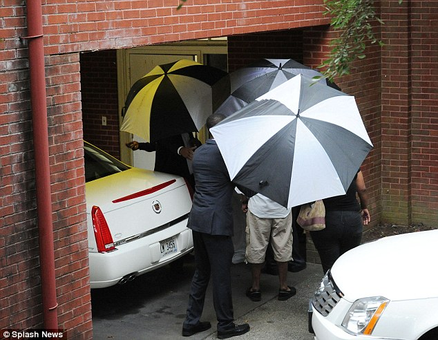 Privacy: Large monotone umbrellas were put up to shroud relatives as they entered and exited