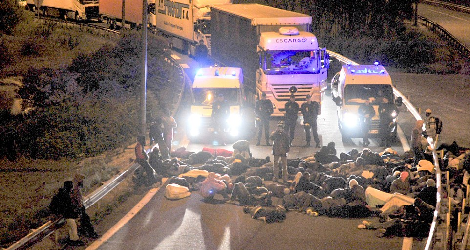 Sit-in: French police watch as the crowd of migrants blocks an access road causing a long queue of lorries