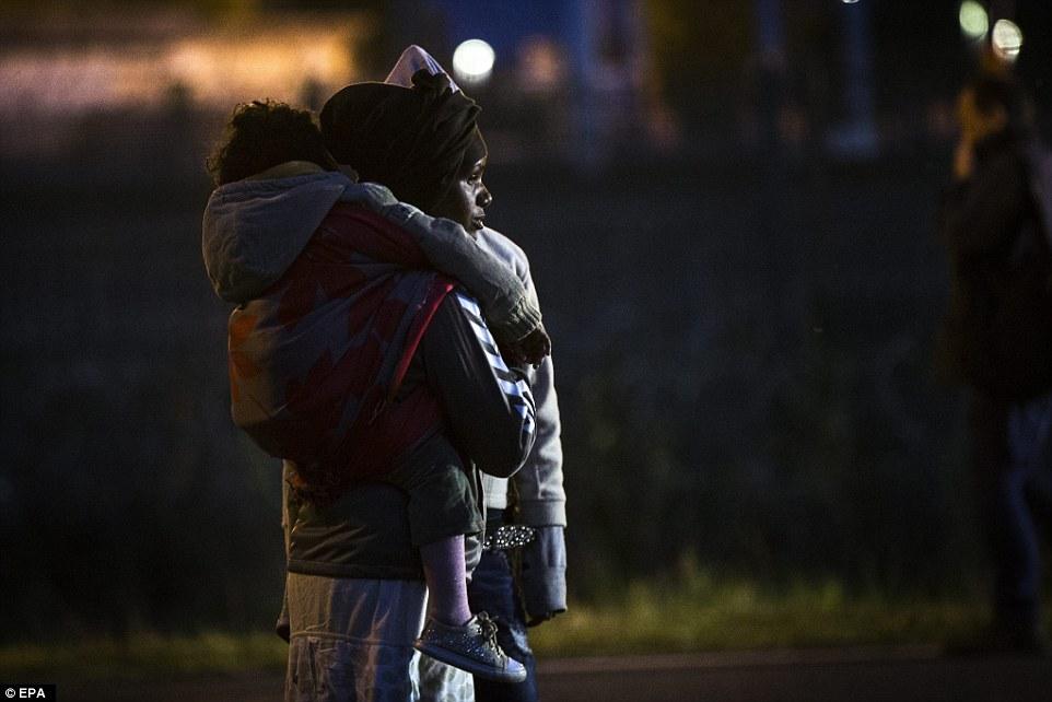 En espera: Una madre de Eritrea espera con su hijo por la oportunidad de cruzar la valla y llegar a las pistas