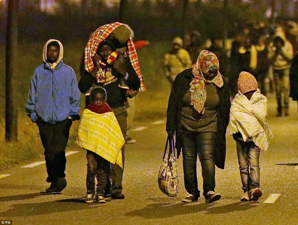 Moviéndolos en: Migrantes - incluyendo niños pequeños - moveros de la valla perimetral del sitio de Eurotunnel en Calais, como policía francesa hacen sus redadas nocturnas de la zona ayer por la tarde