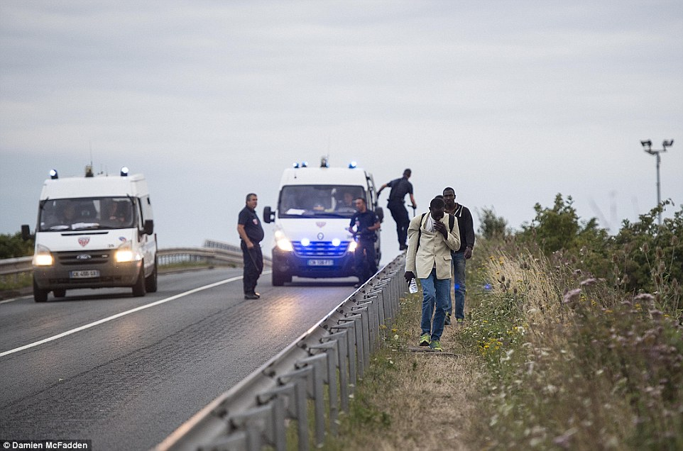Observar: Los migrantes a pie por un camino que conduce al túnel de la Mancha en Calais anoche mientras la policía se ven en