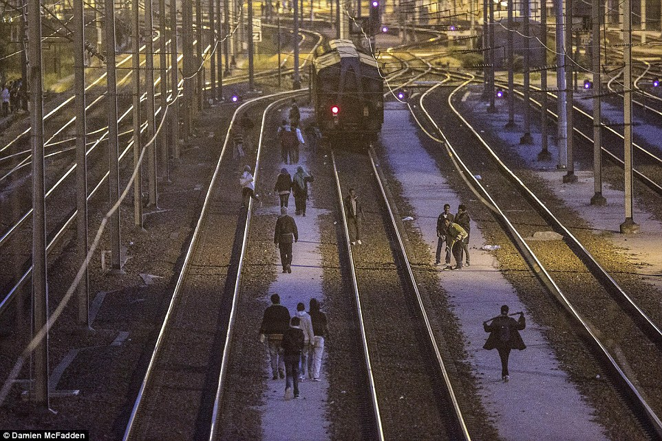 El asalto del túnel: Los migrantes fueron vistos tratando de hacer su camino hacia el Reino Unido a través del Eurotúnel en Calais ayer por la tarde.  Un 'túnel de inspección imprevista' retrasó servicios Eurotunnel esta mañana