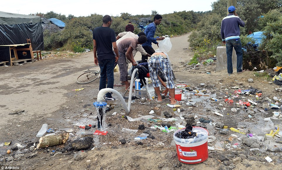 Los migrantes utilizan un grifo de agua para lavar a un claro basura esparcida en un campamento de migrantes cerca de Calais