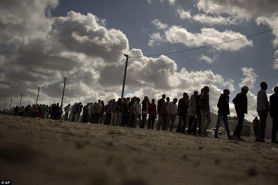 Colas masivas: Los migrantes hacen cola para recibir raciones de alimentos a un campamento de inmigrantes en Calais esta mañana
