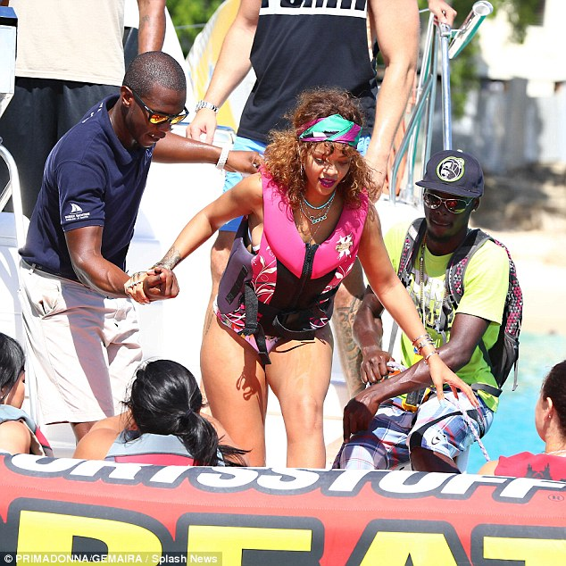 Helping hand: Rihanna also needed some assistance when making her way on to the catamaran