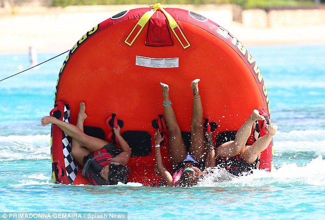 Man down: The singer and her pals tumbled off of the inflatable and into the sea