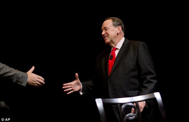 Huckabee shakes hands with Erickson as he steps on to the stage to talk about his plans for America